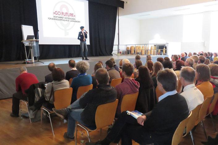 Foto Ulrike Hartmann bei einem Vortrag auf der Bühne
