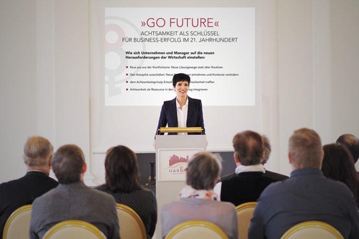 Foto von Ulrike Hartmann bei einem Vortrag am Pult